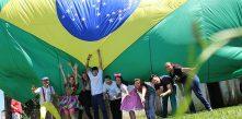 foto de várias pessoas vestidas com roupas de palhaço segurando uma grande bandeira do Brasil
