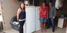 A gestora do PEE e o presidente da Cocel acompanham a entrega da nova geladeira à família de Rosângela (ao centro)