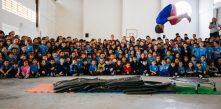 Foto de várias crianças e um professor ao lado do quadro que pintaram no Projeto Tetear