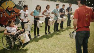 Foto de várias crianças e um professor fazendo aula de percussão no Projeto Tetear
