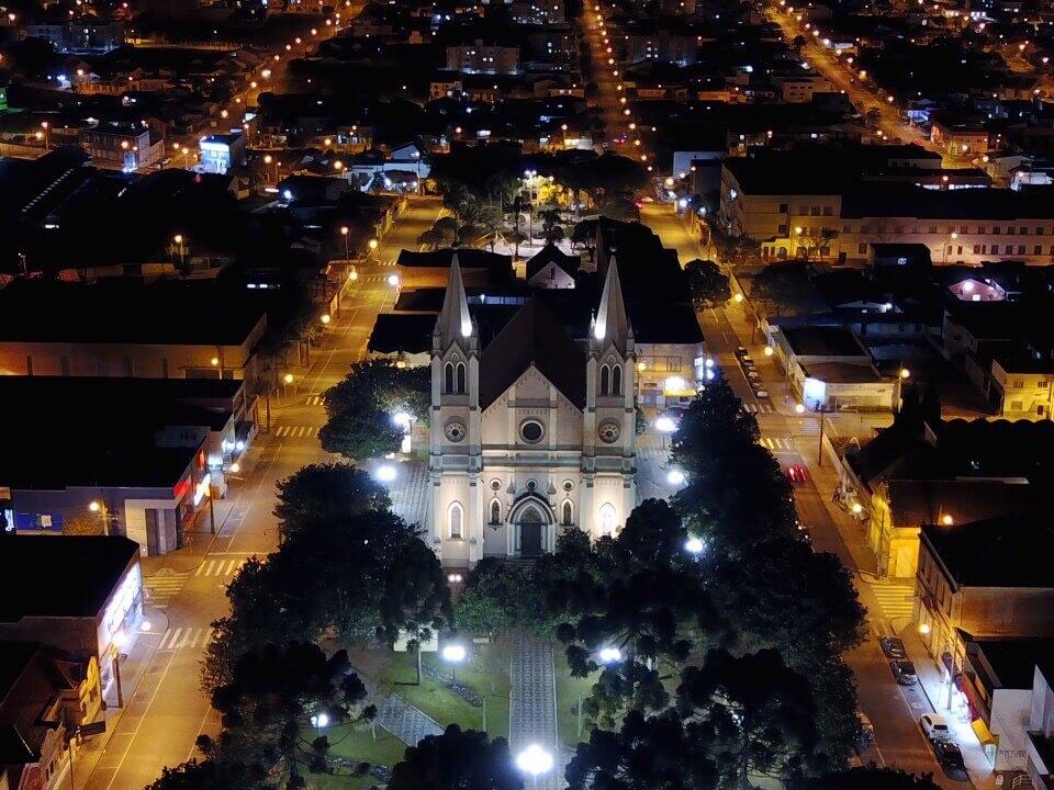 Foto aérea mostrando a Igreja Matriz de Campo Largo, destacando a iluminação pública feita pela Cocel