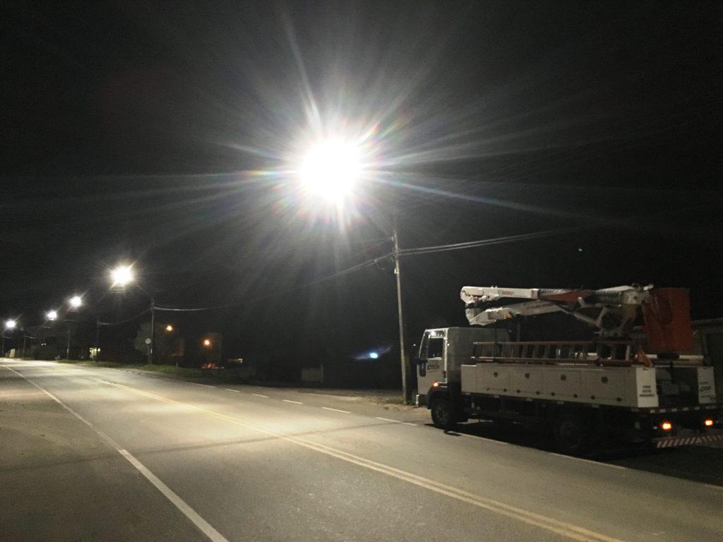 Foto de uma rua em Campo Largo, destacando os postes de iluminação pública com as luzes acesas. No canto direito da imagem aparece o caminhão de serviços da Cocel estacionado.